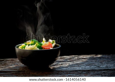 The steam from the vegetables broccoli cauliflower on black bowl , a steaming. Boiled hot Healthy food on table on black background,hot food and healthy meal concept #1614056140