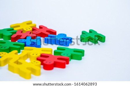 Close-up view from the top of a children's toy-constructor made of natural wood in the form of small people of different colors with a smile on a white isolated background. A group of small toy smiles #1614062893