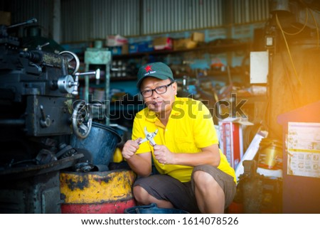 Vietnamese repairman wears a yellow shirt with a hand tool Wearing a Vietnam military hat #1614078526