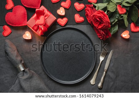 Valentine's day or birthday romantic dinner. Romantic table setting with champagne, red rose on black linen tablecloth. View from above. #1614079243