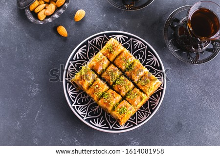 Baklava. Ramadan Dessert. Traditional Arabic dessert with nuts and honey, cup of tea on a concrete table. Top view #1614081958
