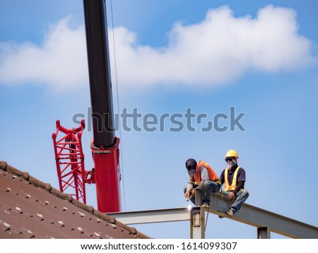 Two builders welding steel on high-rise steel frame without safety belt on construction site with blue sky background. Construction industrial. Copy space. #1614099307
