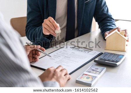 Sale purchase contract to buy a house, Real estate agent are presenting home loan and giving keys to customer after signing contract to buy house with approved property application form. #1614102562