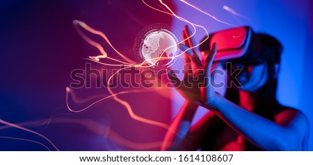 Young woman using glasses of virtual reality on dark background. Smartphone using with VR headset,virtual reality,future technology concept.Asian woman using VR glasses in colorful neon lights. #1614108607
