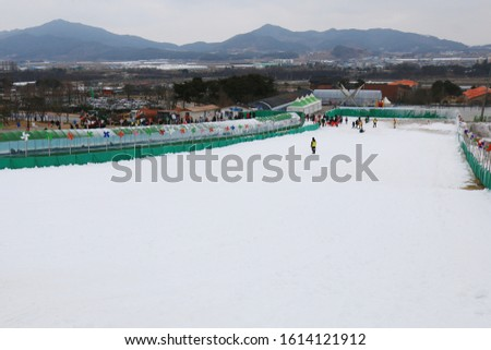 This is the full picture of the sledding slope. And far away, yellow clad safety guards are guiding people.