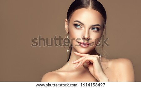 Beautiful girl . Fashionable and stylish woman in trendy jewelry big earrings .  Fashion look  , beauty and style. Natural makeup & easy styling Royalty-Free Stock Photo #1614158497