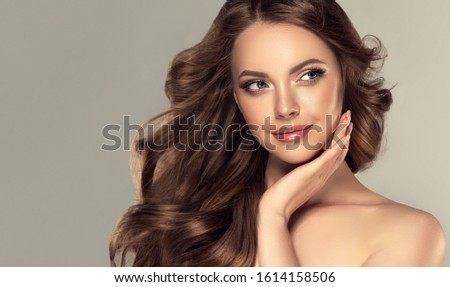 Beauty brunette girl with long  and   shiny wavy black hair .  Beautiful   woman model touching her face with curly hairstyle . Royalty-Free Stock Photo #1614158506