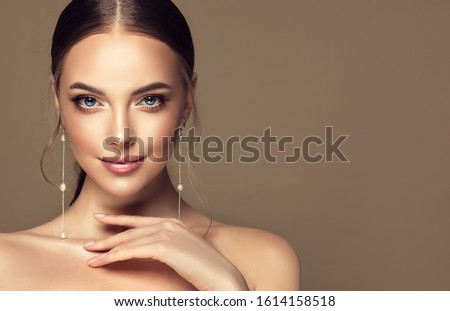 Beautiful girl . Fashionable and stylish woman in trendy jewelry big earrings .  Fashion look  , beauty and style. Natural makeup & easy styling Royalty-Free Stock Photo #1614158518