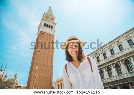 smiling pretty caucasian woman rise up hands at venice city square bell tower on background