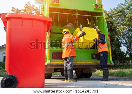Two garbage men working together on emptying dustbins for trash removal with truck loading waste and trash bin. #1614243901