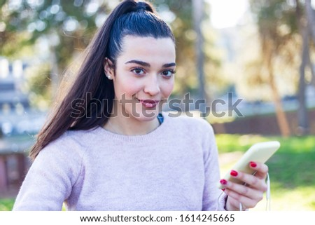 Portrait of a young beautiful brunette with ponytail outdoors holding a phone while looking camera #1614245665