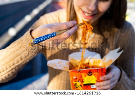 Girl eating Chinese noodles with some blue chopsticks. Concept of chopsticks. #1614261916