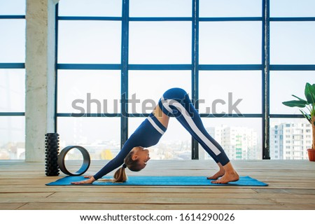 Yoga asana Indoor before a large panoramic window. Sports recreation. Beautiful young woman in yoga pose. Individual sports. Royalty-Free Stock Photo #1614290026