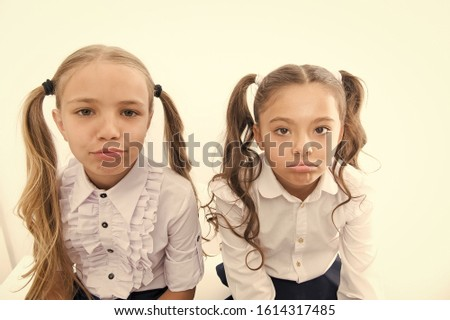 Unhappy cuties. Unhappy little schoolchildren isolated on white. Adorable small girls with unhappy emotions looking in camera. Unhappy because of school starts. #1614317485