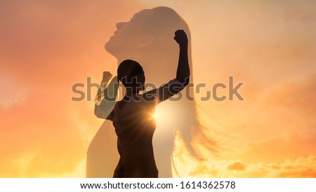 Strong woman, winning, success , and life goals concept. Young woman with arms flexed looking up to the sky. Royalty-Free Stock Photo #1614362578