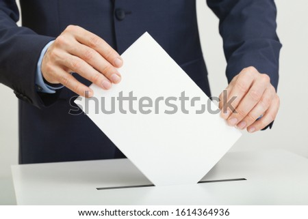 Caucasian male in suit holding ballot paper in hand and throwing it into election box #1614364936