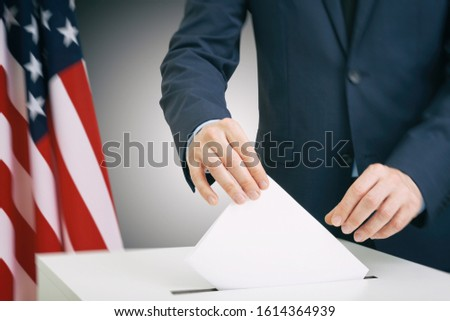 Man in suit holding ballot paper in hand and throwing it into election box with USA flag on background #1614364939