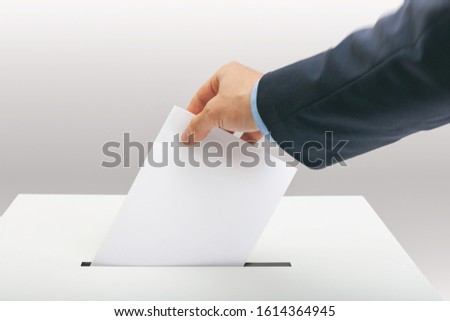 Caucasian male in suit holding ballot paper in one hand and throwing it into election box #1614364945