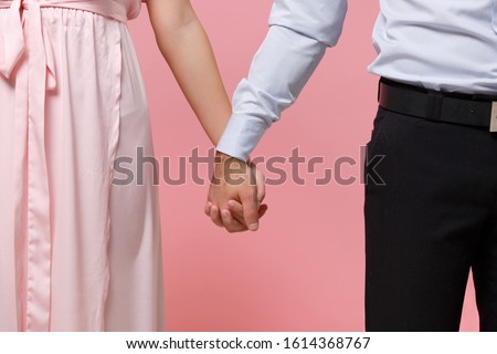 Cropped image of young couple two guy girl in party outfit celebrating posing isolated on pastel pink background in studio. Valentine's Day Women's Day birthday holiday concept. Holding hands folded