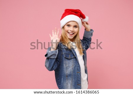 Pleasant little kid girl 12-13 years old in Christmas hat isolated on pastel pink background. New Year 2020 celebration party concept. Mock up copy space. Waving greeting with hand as notices someone #1614386065