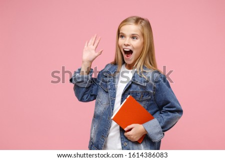 Excited little kid girl 12-13 years old in denim jacket isolated on pastel pink background. Childhood lifestyle concept. Mock up copy space. Hold notebook waving greeting with hand as notices someone #1614386083