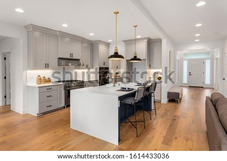 Kitchen in new luxury home with waterfall island, stainless steel appliances, pendant lights, and hardwood floors #1614433036