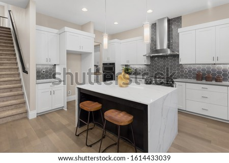 Kitchen in new luxury home with waterfall island, stainless steel appliances, pendant lights, and hardwood floors #1614433039