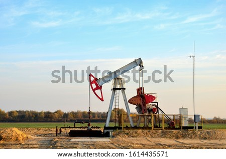 Oil drilling derricks at desert oilfield for fossil fuels output and crude oil production from the ground. Oil drill rig and pump jack on the background, sunset. Belarus, Rechitsa region