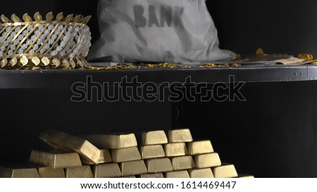 The shelf with gold coins and paper currency, and with the money bag, articles of jewelry and gold blocks in the bank safe. #1614469447