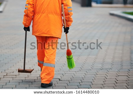 Municipal worker sweep city street,  janitor with broomstick and scoop for garbage in hands. Municipal worker in orange uniform collecting garbage from road and sidewalk. City cleaning service #1614480010