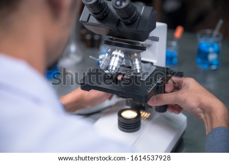 Young scientist looking through a microscope in a laboratory. Young scientist doing some research. #1614537928