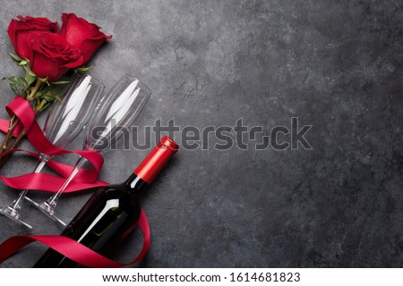 Valentines day greeting card with rose flowers and red wine bottle on stone background. Top view flat lay with space for your greetings #1614681823