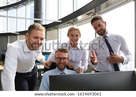 Group of young modern people in formalwear using modern technologies while working in the creative office #1614693061