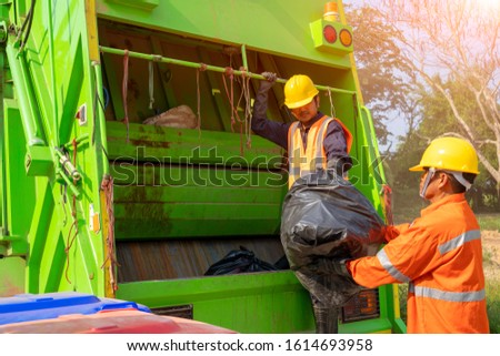 Two garbage men working together on emptying dustbins for trash removal with truck loading waste and trash bin. #1614693958