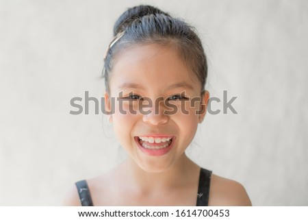 portrait of a happy smiling beautiful and confident child girl, laughing child expressive facial expressions, space for text, joy on the kid face on a light background, fun and joyful concept #1614700453
