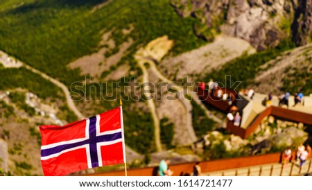 Trollstigen mountain road landscape in Norway, Europe. Norwegian flag waving and many tourists people on viewing platform in background. National tourist route. #1614721477