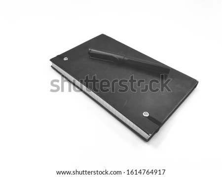 Black old diary on white background and pen #1614764917