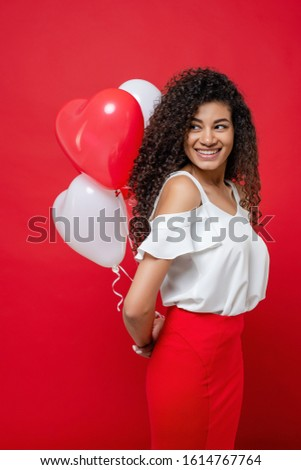 playful cheerful black woman holding colorful balloons isolated on red #1614767764