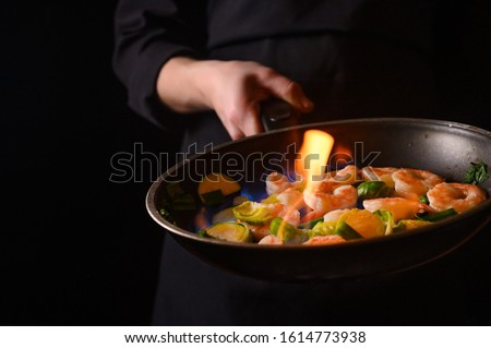 Professional cook cooks shrimps with vegetables on fire. Cooking seafood #1614773938