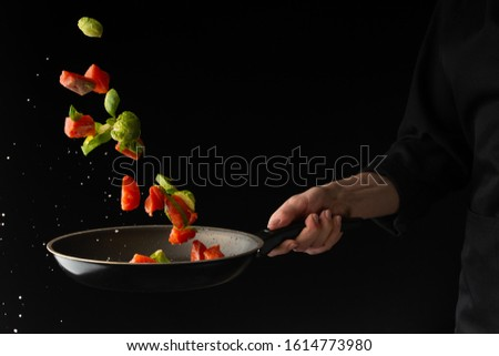 sea ​​or ocean food. Frying in a pan of salmon, with vegetables. Useful and tasty food. Culinary and gastronomy. Freezing in motion. On a black background, horizontal photo. #1614773980