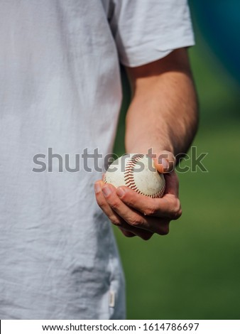 baseball pitcher young man holding baseball in his hand ready to throw
