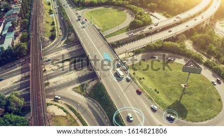 Autonomous Self Driving Cars Concept. Aerial view of cars and buses moving on city intersection and Artificial Intelligence scans road with sensors and control vehicles in traffic. Future Transport #1614821806
