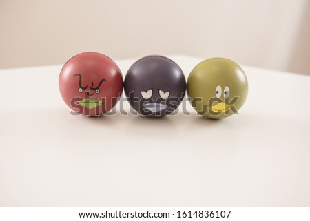 Small balls with faces and different emotions. The emotions are angry, sad and interessted. #1614836107