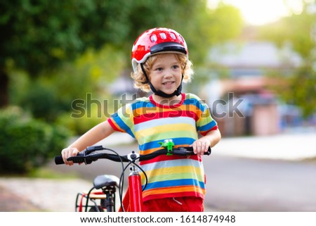 Kids on bike in park. Children going to school wearing safe bicycle helmets. Little boy biking on sunny summer day. Active healthy outdoor sport for young child. Fun activity for kid #1614874948