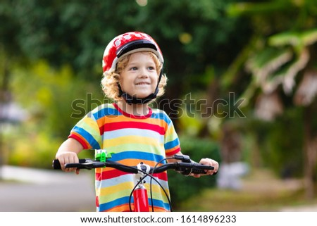 Kids on bike in park. Children going to school wearing safe bicycle helmets. Little boy biking on sunny summer day. Active healthy outdoor sport for young child. Fun activity for kid #1614896233
