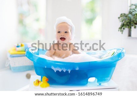 Happy laughing baby taking a bath playing with foam bubbles. Little child in a bathtub. Smiling kid in bathroom with colorful toy duck. Infant washing and bathing. Hygiene and care for young children. #1614896749