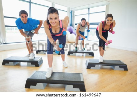 Full length of instructor with fitness class performing step aerobics exercise with dumbbells in a gym #161499647