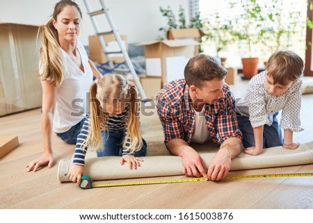 Parents and two children roll out a carpet in the new house as a home #1615003876