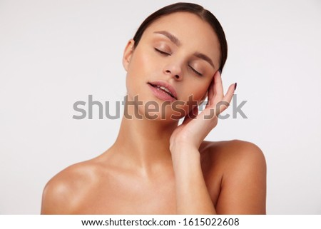 Pleasant looking young dark haired female with casual hairstyle touching gently her face and keeping eyes closed while standing against white background #1615022608