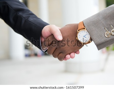 African businessman's hand shaking white businessman's hand  making a business deal. #161507399